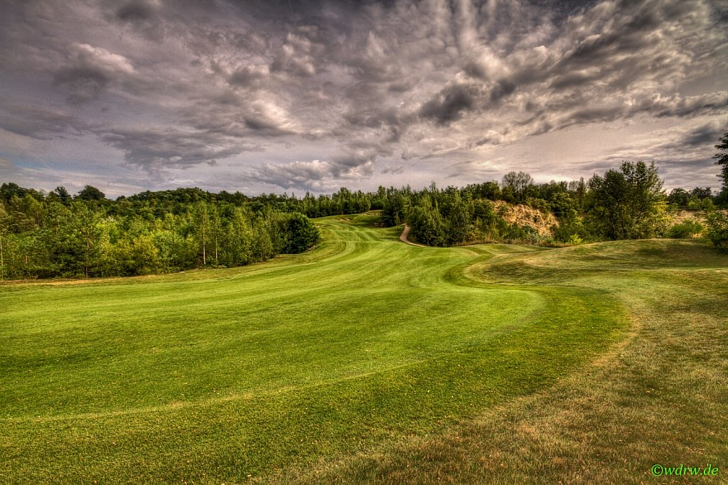 Golfplatz mit dramatisch wirkendem Himmel